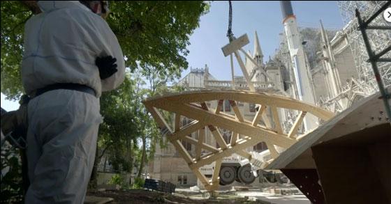 Aux pieds de la cathédrale incendiée le 15 avril 2019, un charpentier fait hisser des cintres de bois. © CFRT / Les piliers de Notre-Dame
