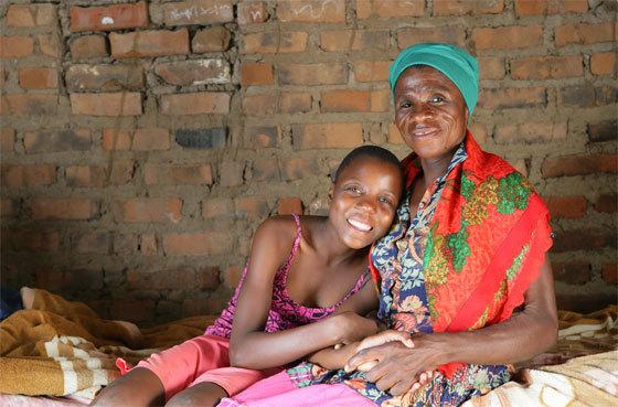Monica, séropositive, et sa petite-fille Sympathy Tshuma, 14 ans, sont assises chez elles sur un lit, dans le village de Makuzeze à environ 200 kilomètres au sud de Bulawayo, la deuxième plus grande ville du Zimbabwe. L'aide aux adolescents sur les questions de prévention et de traitement est très importante. (UNICEF/G. Pirozzi)