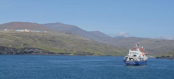 """Le navire """"Marion Dufresne"""" approche de l'île. Au loin la base scientifique Alfred Faure. Photo : B. Crenan"""